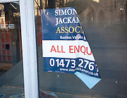 Old 'All enquiries' estate agency poster in empty shop window, Ipswich, England