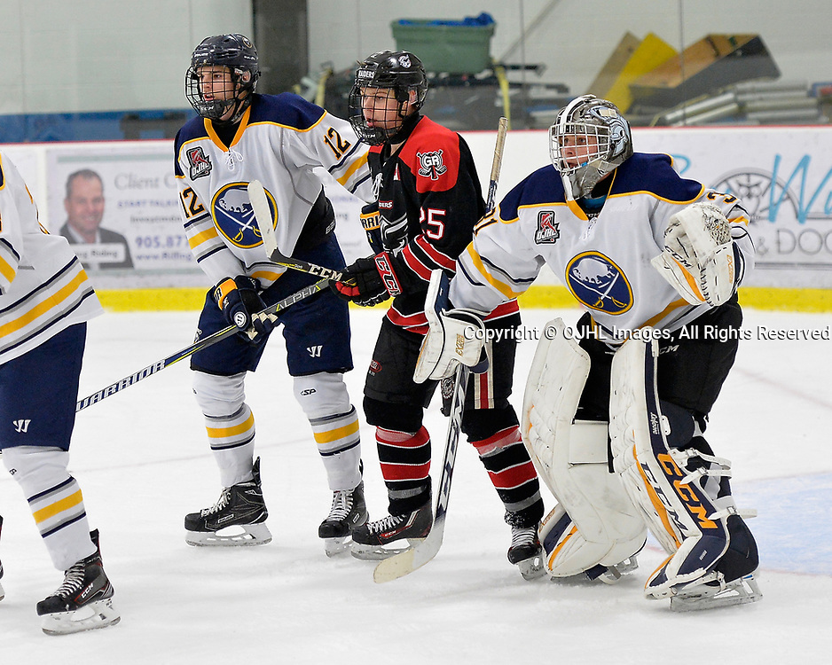 GEORGETOWN, ON  - NOV 4,  2017: Ontario Junior Hockey League game between the Georgetown Raiders and Buffalo Jr. Sabres. Ryan Sidorski #12 of the Buffalo Jr. Sabres and Justin Paul #25 of the Georgetown Raiders battle for position beside goaltender Brian George #31 during the third period.<br /> (Photo by Shawn Muir / OJHL Images)