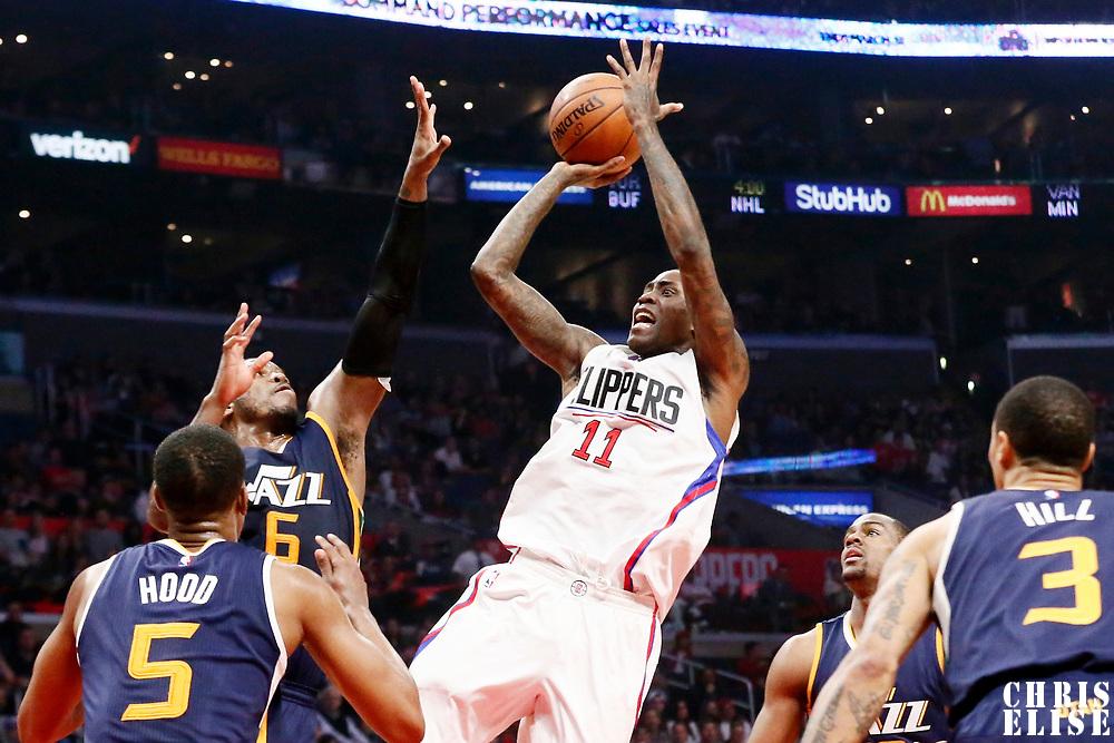 25 March 2016: LA Clippers guard Jamal Crawford (11) takes a jump shot over Utah Jazz forward Joe Johnson (6) and Utah Jazz guard Rodney Hood (5) during the Los Angeles Clippers 108-95 victory over the Utah Jazz, at the Staples Center, Los Angeles, California, USA.