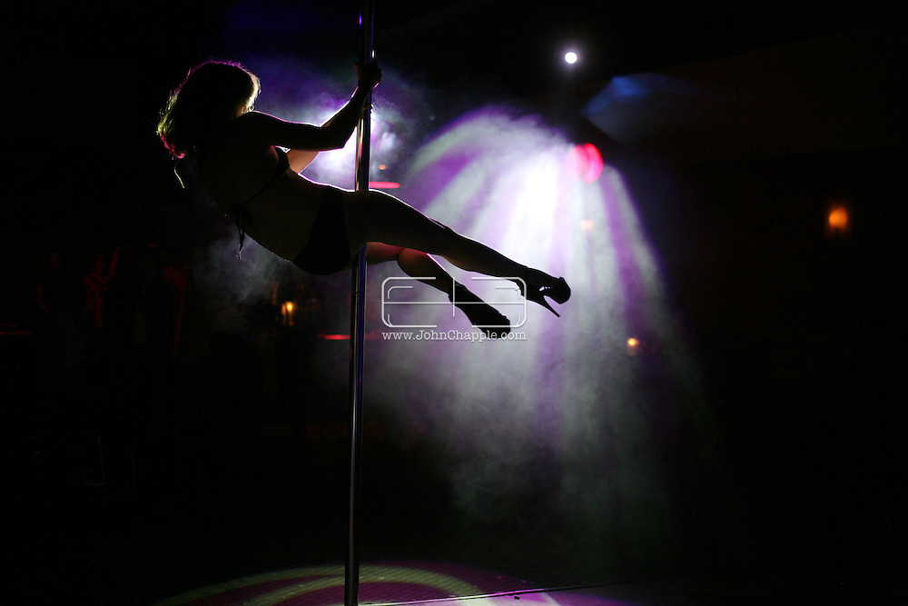 "27th July 2009. Los Angeles, California. In recent years, pole dancing has gained acceptance as a form of physical fitness and even a competition sport. The weekly showcase at Club Good Hurt in West Los Angeles represents the latest evolution in pole dancing's migration from the strip club to the mainstream performance venue. It features Southern California pole dancers performing to live rock music in a setting where, according to show producer Emilee Wilson, there's ""no tipping and no stripping."".PHOTO © JOHN CHAPPLE / www.chapple.biz.tel +1 310 570 9100    john@chapple.biz"