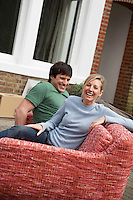 Couple sitting on sofa outside house