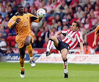 Photo: Daniel Hambury.<br /> Southampton v Wolves. Coca Cola Championship.<br /> 06/08/2005.<br /> Southampton's Dennis Wise and Wolves' Seyi Olofinjana compete for the ball.