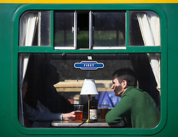 © Licensed to London News Pictures. 07/03/2014. Hampshire, UK. Two men aboard a train drinking pints of real ale at Ropley Station today, 7th March 2014, which is the first day of the 'spring steam gala' on the Watercress Line. The railway line, operated by Mid Hants Railway Ltd, passes between Alresford and Alton in Hampshire. The line is named after its use in the past for transporting freshly cut watercress from the beds surrounding Alresford to London. Photo credit : Rob Arnold/LNP