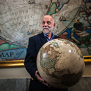 WASHINGTON, DC -- JANUARY 2: Juan Valdes is The Geographer and Director of Editorial and Research at National Geographic Maps. He poses with a globe in front of the Map of Discovery, Western Hemisphere by Newell Convers Wyeth, commissioned by National Geographic in 1927. As a child, he emigrated to Miami from Cuba after the Bay of Pigs and grew up in the U.S. Recently he returned to Cuba for the third time, seeking answers about his past…. (photo by Andre Chung for The Washington Post)