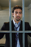 Mid-adult businessman standing behind cell bars