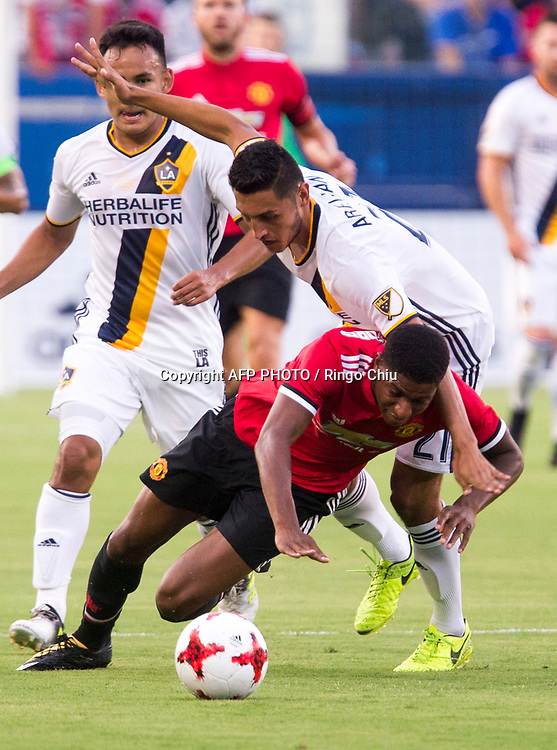 Manchester United Marcus Rashford, bottom, and Los Angeles Galaxy Hugo Arellano battle for the ball during the first half of a national friendly soccer game at StubHub Center on July 15, 2017 in Carson, California.   AFP PHOTO / Ringo Chiu
