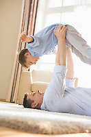 Side view of playful father picking up son while lying on floor at home