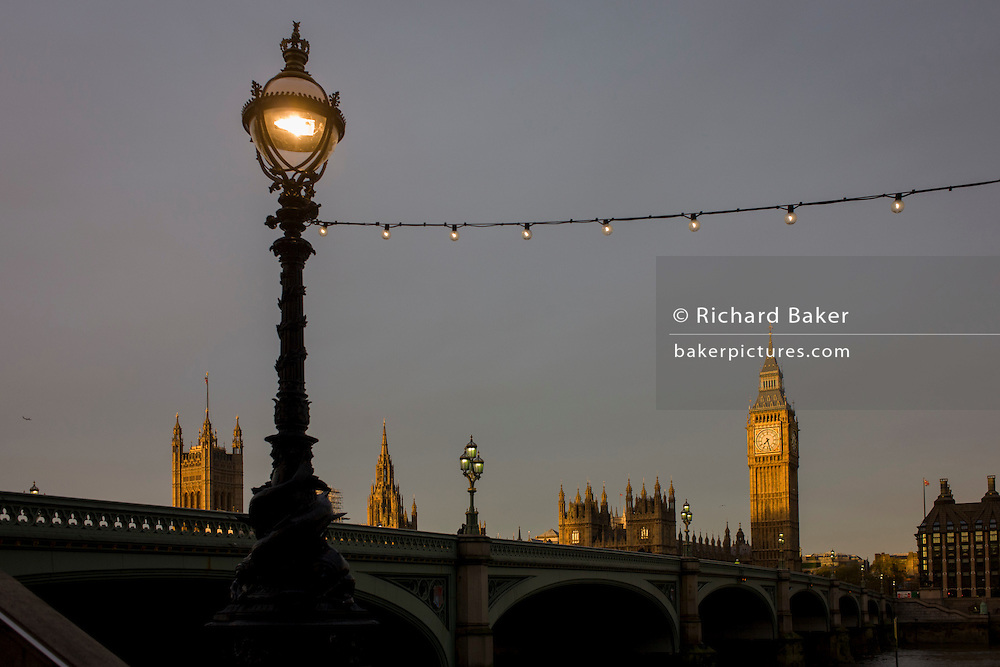 Dawn light on the Palaces of Westminster, Britain's parliament building on the far side of Westminster Bridge on the River Thames.