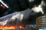 Israel, Galilee, a raging wild fire in an agricultural packing plant. A jet of water from the left is aimed at the flames