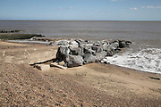 Rock armour reinforcing old concrete groyne on beach. Coastal defences, Felixstowe, Suffolk, England