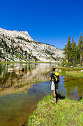 Hiker at Elizabeth Lake under Unicorn Peak, Tuolumne Meadows, Yosemite National Park, California USA