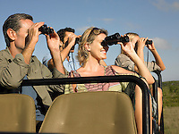 Group of tourists on safari sitting in jeep looking through binoculars close-up