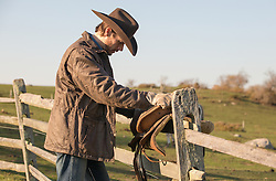 rugged cowboy leaning on a fence at a ranch
