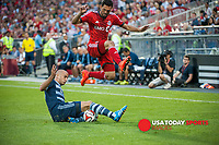 Jul 26, 2014; Toronto, Ontario, CAN; Toronto FC forward Gilberto (9) jumps over the leg of Sporting KC mid-fielder Aurelian Collin( 78) in second half at BMO Field - Sporting KC beat Toronto FC 2 - 1 Mandatory Credit: Peter Llewellyn-USA TODAY Sports