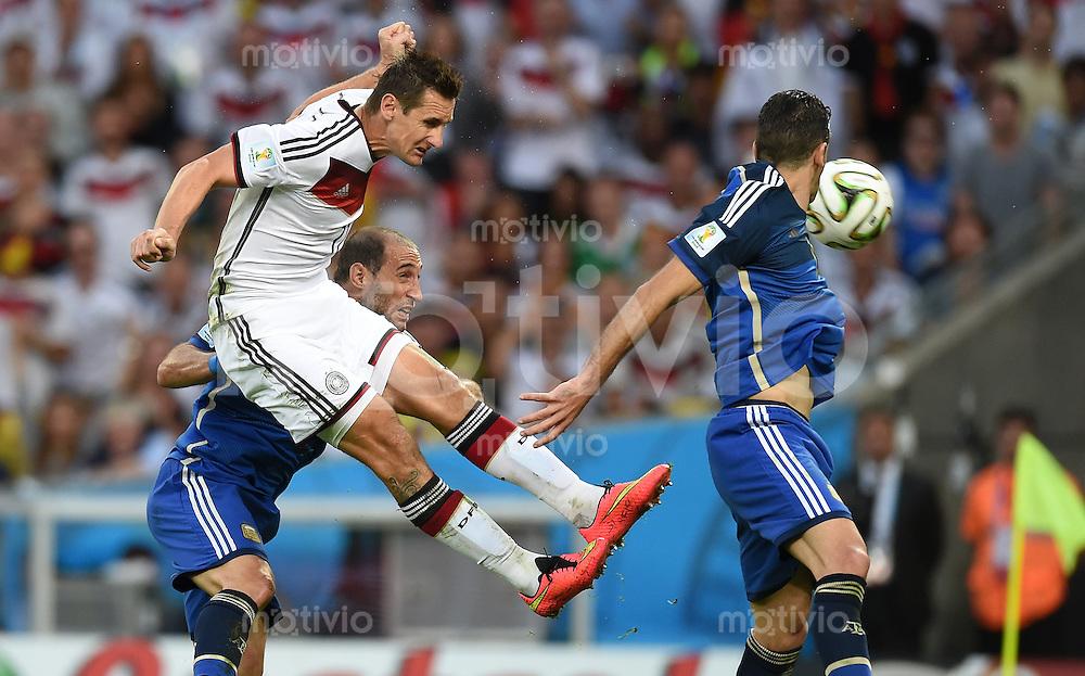 FUSSBALL WM 2014                FINALE Deutschland - Argentinien     13.07.2014 Miroslav Klose (Mitte, Deutschland) koepft vor Pablo Zabaleta (li) und Martin Demichelis (re, beide Argentinien)