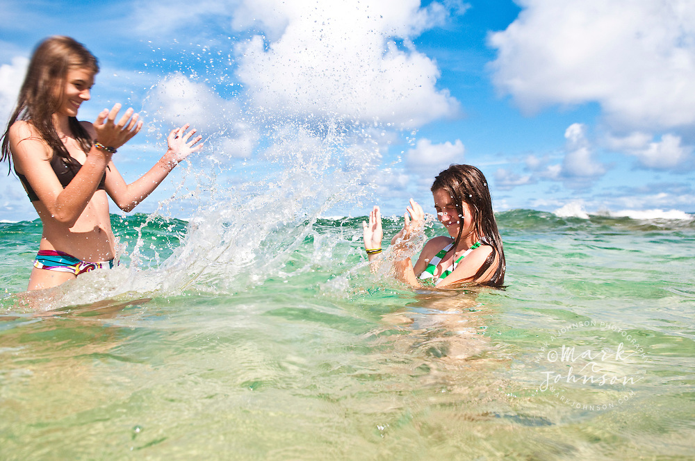 2 Teenage girls splashing water on each other at beach, Kauai, Hawaii, USA