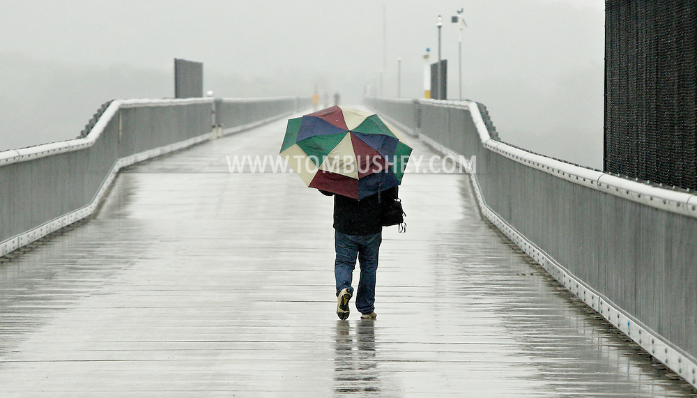 Jeff Penny of Lagrangeville walks across the Walkway over the Hudson as rain falls on Thursday, June 13, 2013. Penny was on the walkway to take rainy day photographs.