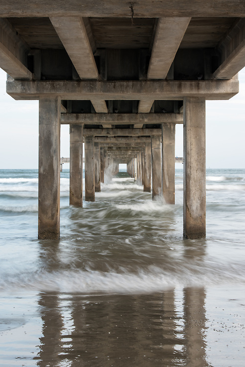 The view of waves crashing underneath Horace Caldwell Pier in Port Aransas, Texas.