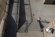 An aerial view of a lady runner stretching on the steps of Fishmongers Hall Wharf in the City of London, on 10th October 2018, in London, England.