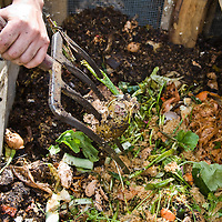 Making compost by adding in raw ingredients and mixing them through the pile.