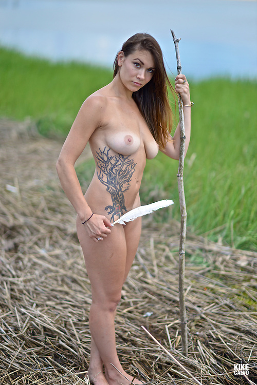 Portrait of a naked brunette American  woman with a tree tatoo.
