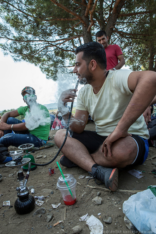 Syrian refugee smoking the small narghile that carries in his luggage, as he is waiting to cross the border.<br /> Refugees arrive at Eidomeni border by bus and some times on foot. There they can cross to the republic of Macedonia on foot.
