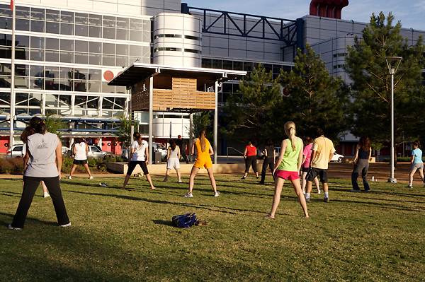Stock photo of people attending outdoor yoga class in the park