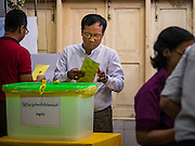 08 NOVEMBER 2015 - YANGON, MYANMAR:  A man drops his completed ballot into the ballot box in central Yangon. The citizens of Myanmar went to the polls Sunday to vote in the most democratic elections since 1990. The National League for Democracy, (NLD) the party of Aung San Suu Kyi is widely expected to get the most votes in the election, but it is not certain if they will get enough votes to secure an outright victory. The polls opened at 6AM. In Yangon, some voters started lining up at 4AM and lines were reported to long in many polling stations in Myanmar's largest city.     PHOTO BY JACK KURTZ