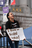 "San Francisco, USA. 19th January, 2019. The Women's March San Francisco begins with a rally at Civic Center Plaza in front of City Hall. A young woman stands on the stage with others representing the Young Women's Freedom Center. She shouts with the crowd and holds a sign reading: ""I stand for chicana women!"" Credit: Shelly Rivoli/Alamy Live News"