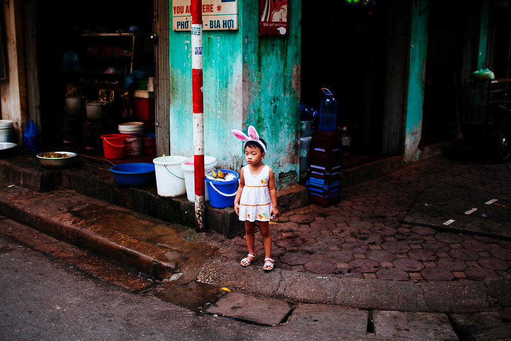 A young girl wearing bunny ears outside on the streets of Hanoi, Vietnam.