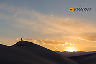 Photograher silhouetted by the sunset at Mesquite Sand Dunes in Death Valley National Park, California, USA