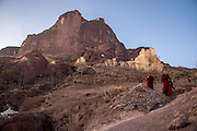Monks walk along a mountain path towards Rabgya monestary, Golok region, Tibet (Qinghai, China). The monestary is home to around 500 monks of the Gelukpa sect.