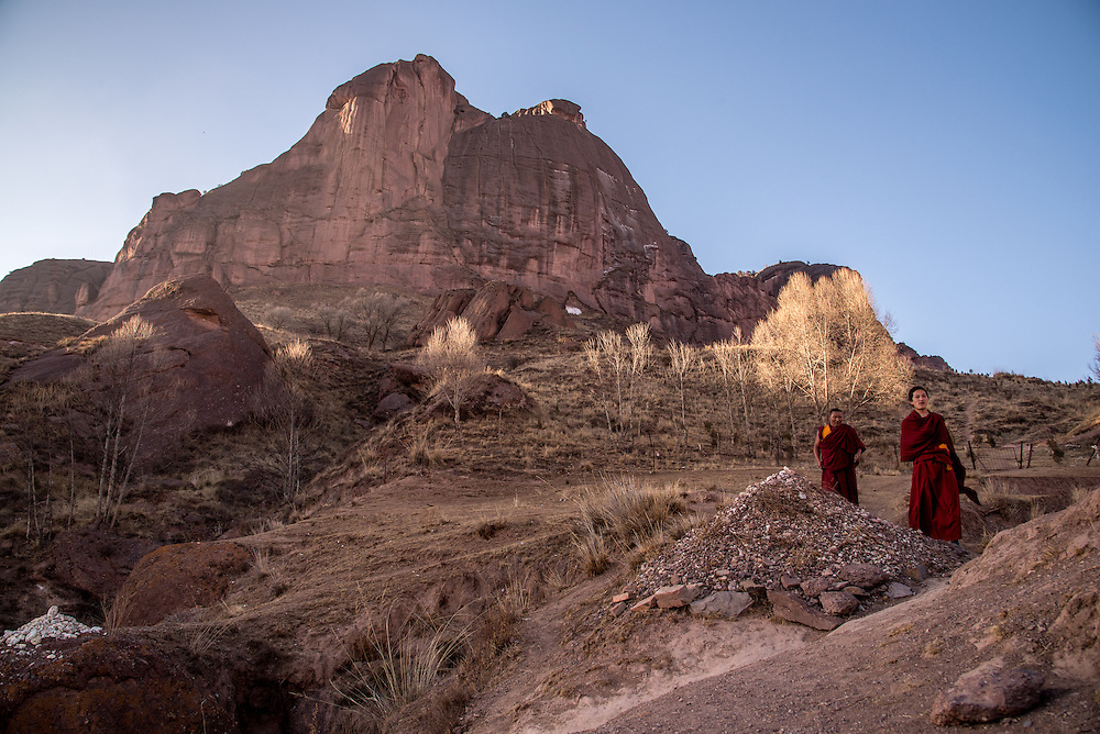 Monks walk along a mountain path towards Rabgya monestary, Golok region, Tibet (Qinghai, China). The monestary is home to around 500 monks of the Gelukpa sect.