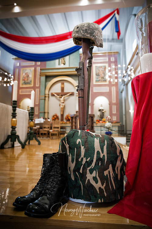 The formation of a fallen soldier's helmet, rifle and boots -- known as a battlefield cross -- sits in the sanctuary of St. Thomas Aquinas Church during the sixth annual Red, White and Blue Mass in Avondale, Ariz., Nov. 6. The Diocese of Phoenix marked the occasion to honor active and retired service men and women and to recall those who died in service to the country. (CNS photo/Nancy Wiechec)