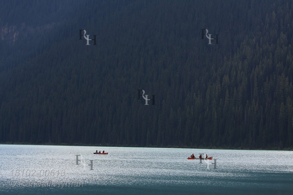 Tourists paddle canoes across Lake Louise in Banff National Park in the Canadian Rockies; Alberta, Canada.