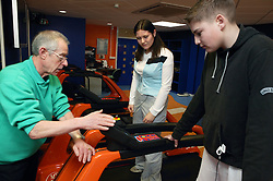 Instructor showing boy and young woman how to use the treadmill at an inclusive fitness gym,