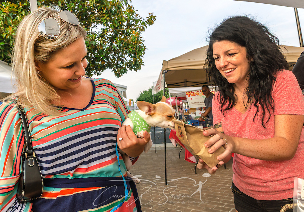 Christine Palmer holds her chihuahua, Carlie, as Kristin Judsky, owner of Azi's Midnight Munchies, lets Carlie sniff a bag of turkey and bacon dog biscuits during the Tucker Farmers Market in downtown Tucker, Georgia, May 22, 2014. The farmers market is held every Thursday from 4-8 p.m. during the growing season. It features products from local farmers and artisans. Judsky started making her all-natural, homemade dog treats seven years ago. (Photo by Carmen K. Sisson/Cloudybright)