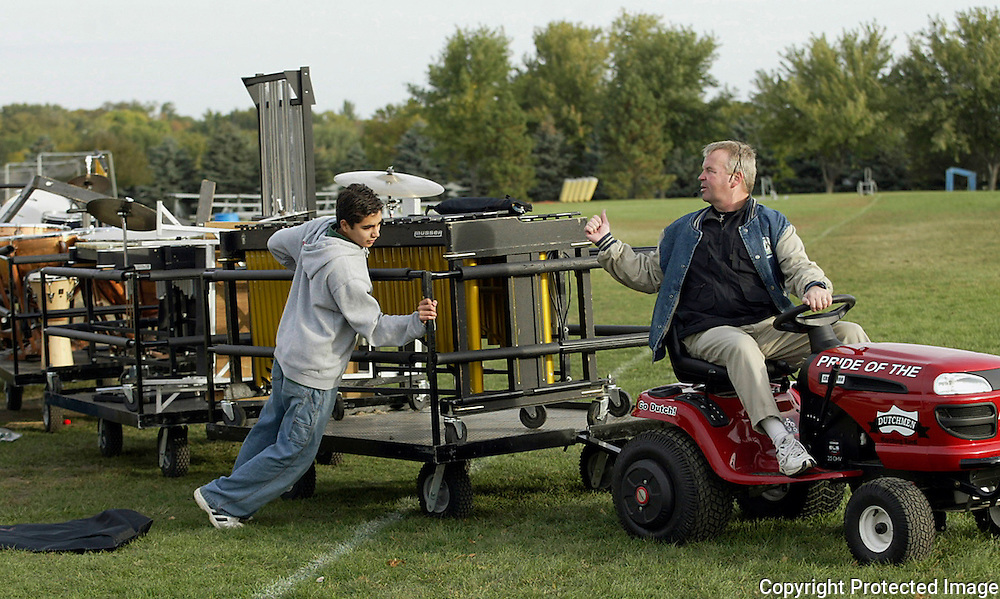 "Freshman Gustavo Vazquez helps band director Steve Connell move band instruments after an early morning practice in October.  ""This is the hardest working group of kids I've had,"" said Connell about his 2003 Pride of the Dutchmen Marching Band.  The material I gave them is so difficult.  I want to be an innovator in Iowa."""