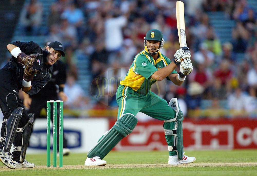 13 February 2004, International one day cricket, Eden Park, Auckland, New Zealand. Match 1 in series of 6, New Zealand vs South Africa..South African batsman Jacques Kallis cuts during his innings of 26 as New Zealand wicketkeeper Brendon McCullum looks on. South Africa won the match by 5 wickets after New Zealand batted first and scored 225- 8 in 50 overs..Please credit: Andrew Cornaga/Photosport