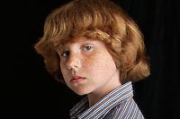 Boy (10-12) on black background portrait close-up