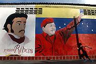 """Un niño corre frente a un mural con imágenes de la """"Misión Ribas"""" y del presidente venezolano, Hugo Chávez ubicado en la parroquia de Catia, al oeste de Caracas. Caracas, 20-10-2005  (ivan gonzalez)"""