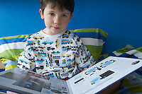 Boy (5-6) sitting in bed reading book portrait