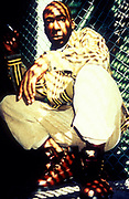 Professor Griff of Public Enemy wearing baggy clothes and red boots next to wire fence, London, U.K, 1980s.