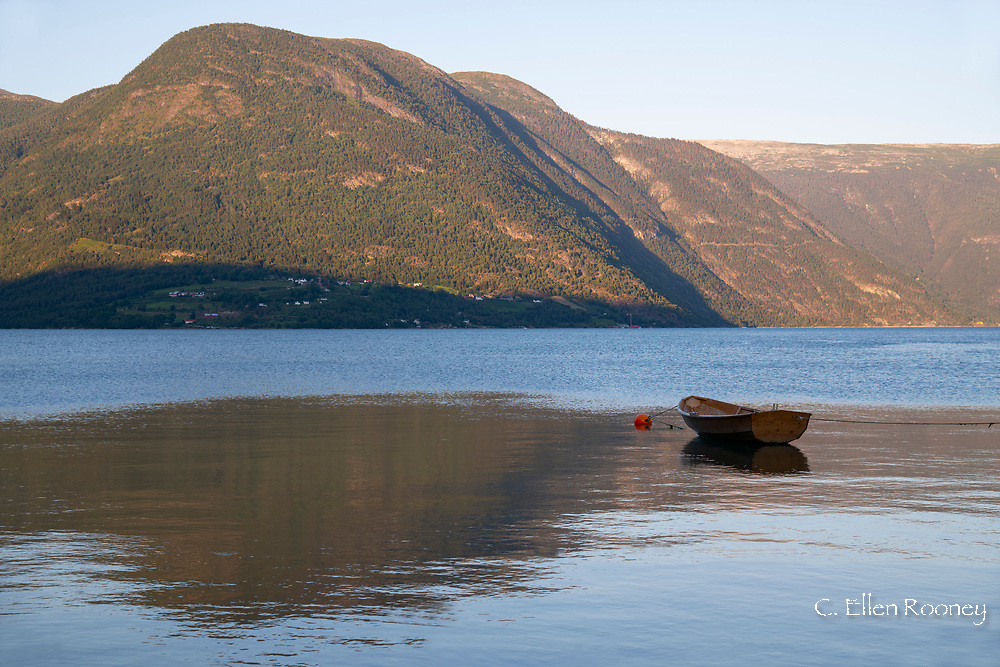 A small wooden boat surrounded by mountains on Lustra Fjord, Vestlandet, Norway