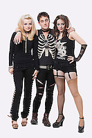 Full length portrait of three young punks over white background