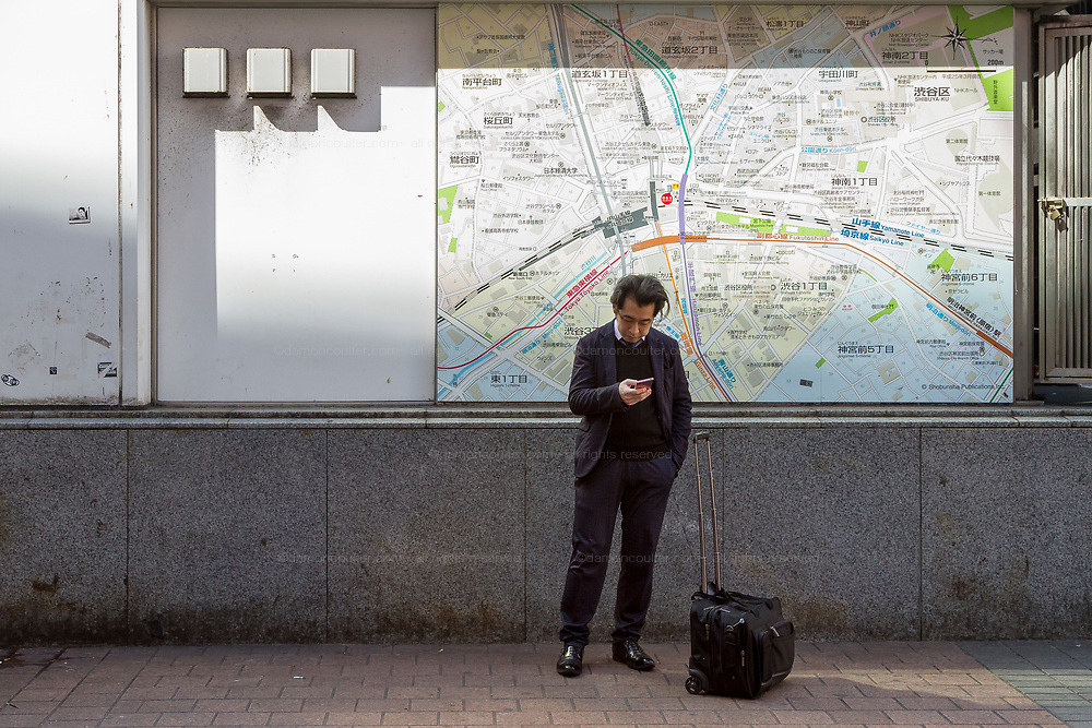 A Japanese man checks his smart phone in front of a map of the Shibuya area. Hachiko Square, Shibuya, Tokyo, Japan, Thursday February 27th 2020