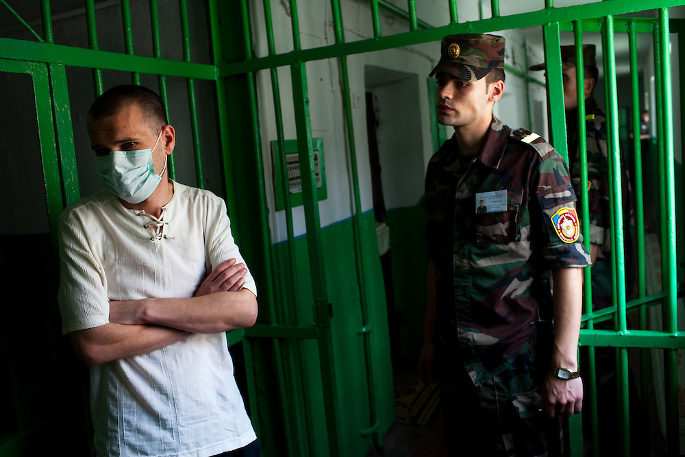 A guard at a prison in Chisinau watches a patient who waits to get his daily TB medicine..
