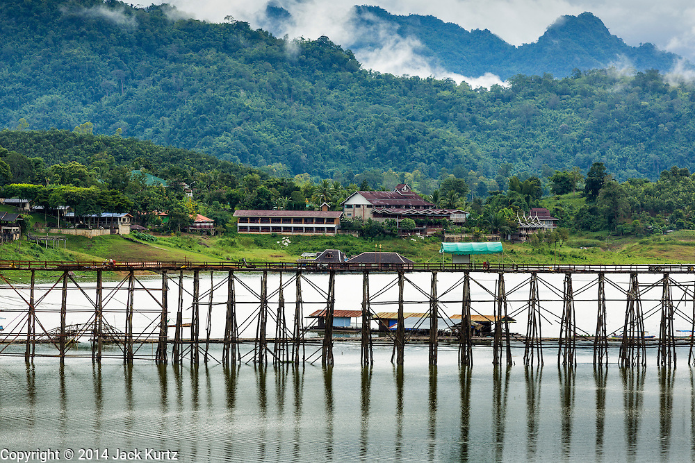 17 SEPTEMBER 2014 - SANGKHLA BURI, KANCHANABURI, THAILAND: The Mon Bridge. The 2800 foot long (850 meters) Saphan Mon (Mon Bridge) spans the Song Kalia River. It is reportedly second longest wooden bridge in the world. The bridge was severely damaged during heavy rainfall in July 2013 when its 230 foot middle section  (70 meters) collapsed during flooding. Officially known as Uttamanusorn Bridge, the bridge has been used by people in Sangkhla Buri (also known as Sangkhlaburi) for 20 years. The bridge was was conceived by Luang Pho Uttama, the late abbot of of Wat Wang Wiwekaram, and was built by hand by Mon refugees from Myanmar (then Burma). The wooden bridge is one of the leading tourist attractions in Kanchanaburi province. The loss of the bridge has hurt the economy of the Mon community opposite Sangkhla Buri. The repair has taken far longer than expected. Thai Prime Minister General Prayuth Chan-ocha ordered an engineer unit of the Royal Thai Army to help the local Mon population repair the bridge. Local people said they hope the bridge is repaired by the end November, which is when the tourist season starts.    PHOTO BY JACK KURTZ