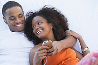 Man listening to mp3 player hugging girlfriend