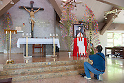 A pilgrim at the alter of the Church of the Divine Providence, where the Martyr Archbishop Oscar Romero was shot and killed in 1980.  El Salvador prepares for the beatification ceremony and mass announcing the beatification of Archbishop Oscar Romero. The Archbishop was slain at the alter of his Church of the Divine Providence by a right wing gunman in 1980. Oscar Arnulfo Romero y Galdamez became the fourth Archbishop of San Salvador, succeeding Luis Chavez, and spoke out against poverty, social injustice, assassinations and torture. Romero was assassinated while offering Mass on March 24, 1980.